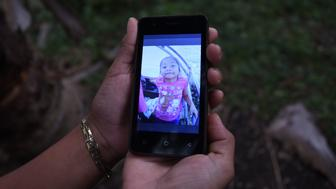 A realtive shows in a mobile phone a picture of 7-year old Jakelin Amei Rosmery Caal, who died in a Texas hospital two days after being taken into custody by border patrol agents in a remote stretch of New Mexico desert- in San Antonio Seacortez village, in Raxruha municipality, Alta Verapaz departament 320 km north Guatemala city on December 15, 2018. (Photo by JOHAN ORDONEZ / AFP)        (Photo credit should read JOHAN ORDONEZ/AFP/Getty Images)
