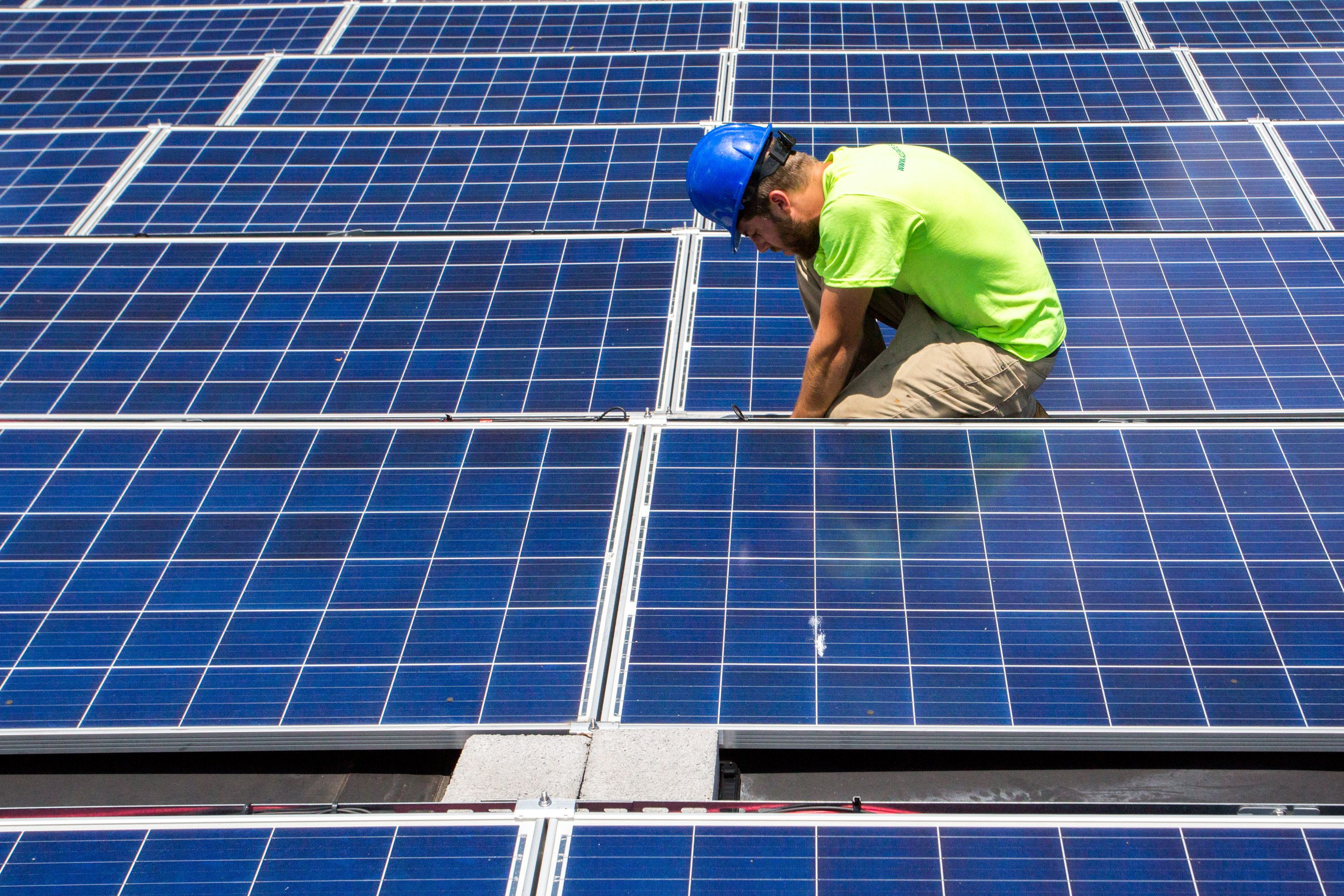 CHARLOTTE NC - June 2, 2017: CREDIT: Mike Catanzaro, panel installer at Accelerate Solar, finishes installed electrical wiring at a solar array he recently installed at a job site in East Charlotte. They are finishing up installing a solar panel array at the Aurora Apartments to help offset electrical demand in certain buildings.  (Photo by Logan Cyrus for The Washington Post via Getty Images)