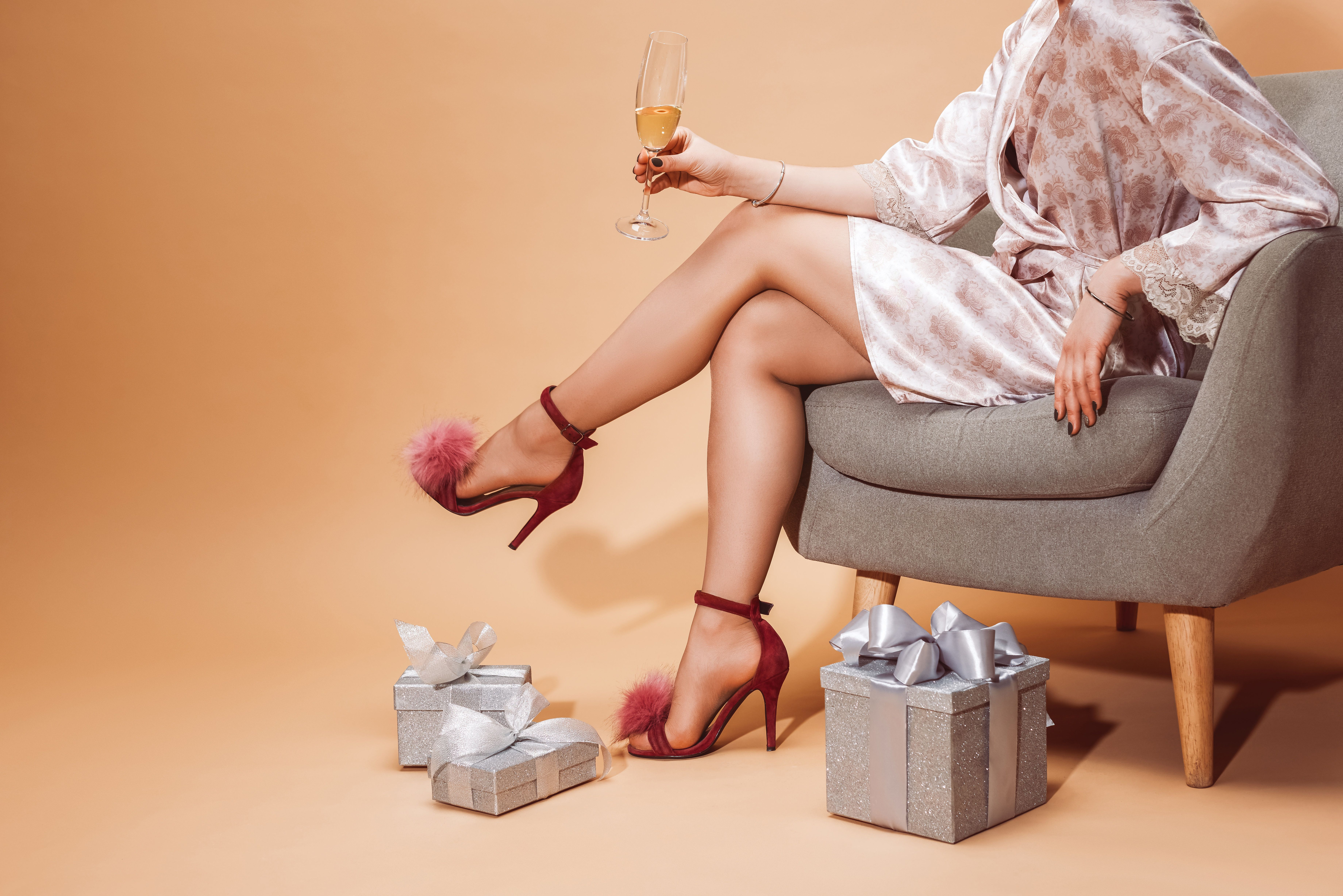 cropped image of woman sitting on armchair and holding glass of champagne on beige
