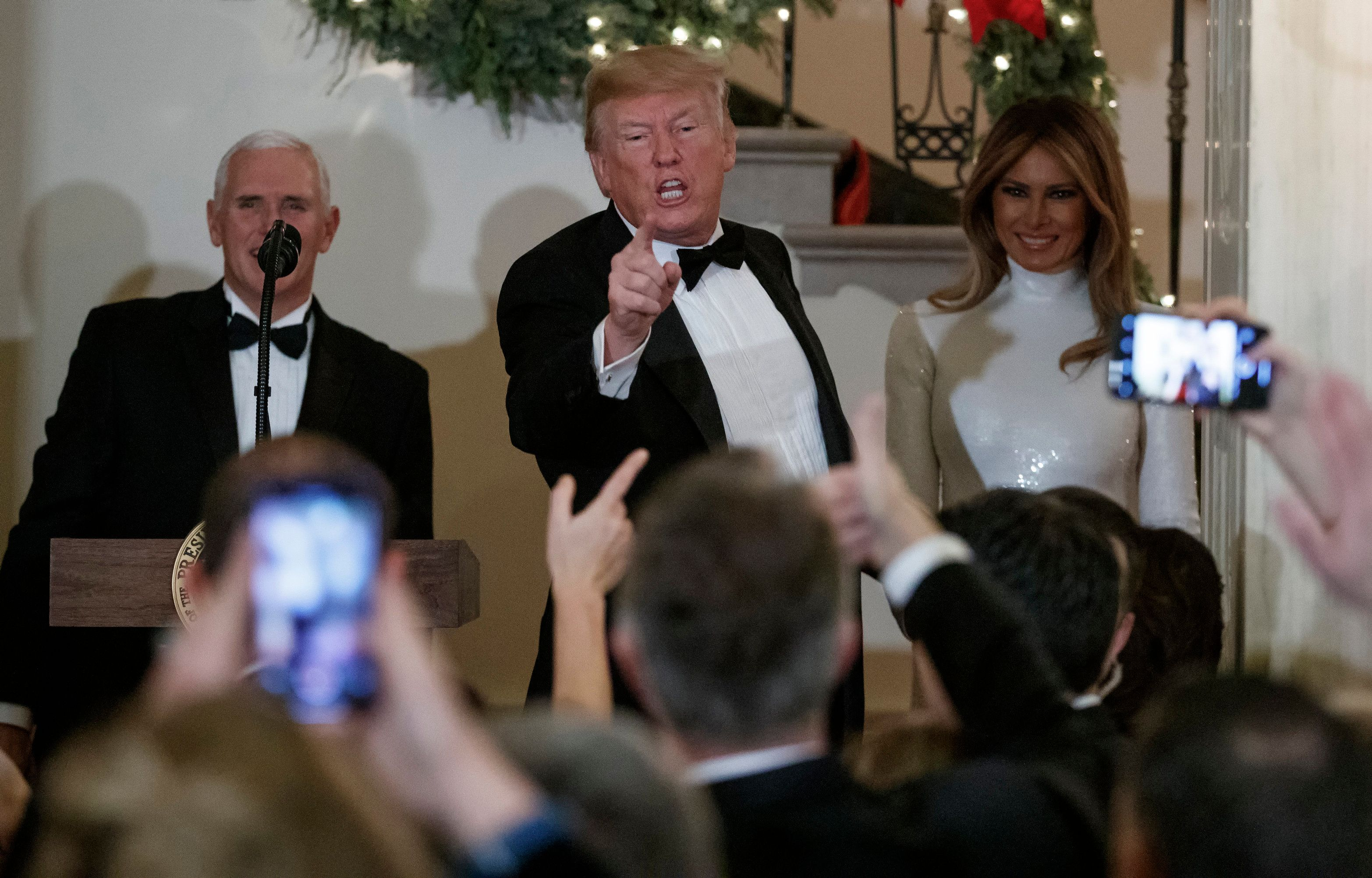 President Donald Trump, joined by Vice President Mike Pence, left, and first lady Melania Trump, right, acknowledges the crowd during the Congressional Ball in the Grand Foyer of the White House in Washington, Saturday, Dec. 15, 2018. (AP Photo/Carolyn Kaster)