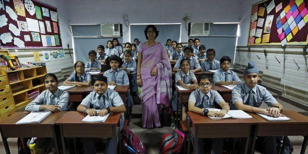 Teacher Archana Shori poses with 7th-grade level students in their classroom at Rukmini Devi Public school...