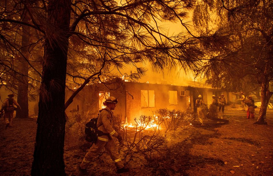 Firefighters work to keep flames from spreading through the Shadowbrook apartment complex as a wildfire...