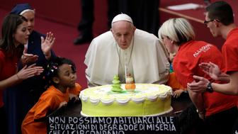 "Pope Francis blows a candle atop of a cake he was offered on the eve of his 82nd birthday during audience with children and family from the dispensary of Santa Marta, a Vatican charity that offers special help to mothers and children in need, in the Paul VI hall at the Vatican, Sunday, Dec. 16, 2018. The writing on the bottom of the cake reads: "" We can not get use to decay and poverty situation that are around us. A Christian must react "". (AP Photo/Gregorio Borgia)"