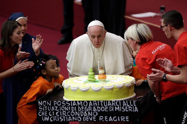 Pope Francis blows a candle atop of a cake he was offered on the eve of his 82nd birthday at the Vatican, Sunday, Dec. 16, 20