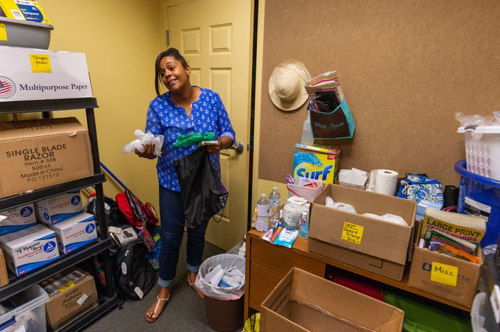 Briana Martin, drop-in center manager at Covenant House, shows the bags of hygienic products that are handed out to at-risk populations in Charleston. The green bag is for people to use to clean up their own waste.