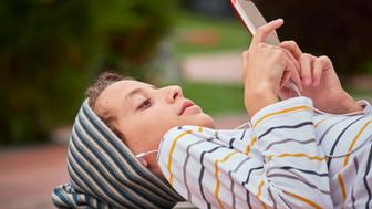 Boy lying down on a concrete bench, using a smartphone and headphones. Self confidence and cheerful attitude. Outdoors photography with natural day lighting. Side view. Horizontal composition. Copy space.