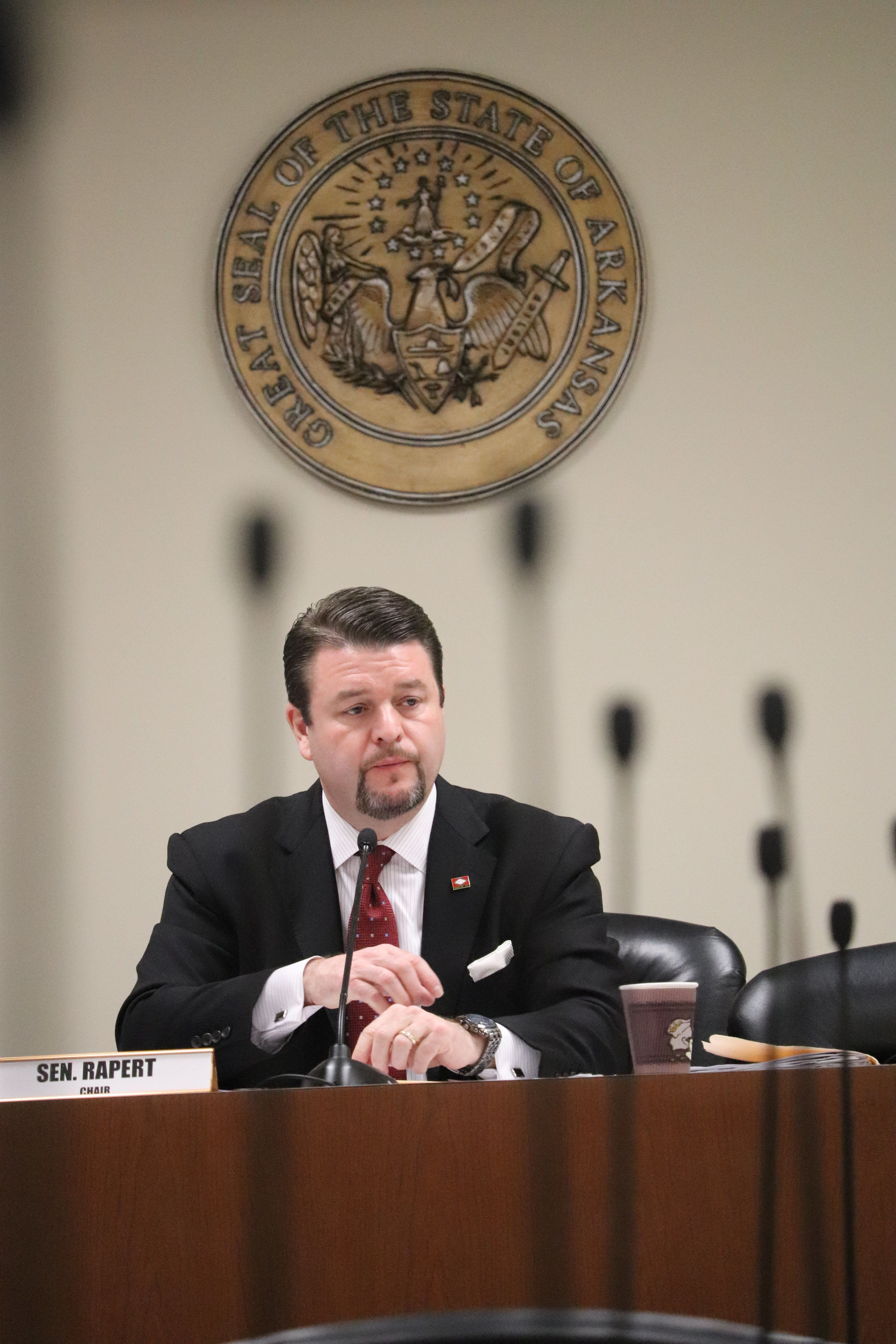 Beyond a number of microphones atop meeting room desks, Sen. Jason Rapert presides Wednesday, March 14, 2018, over a session of the Senate Insurance and Commerce Committee at the state Capitol in Little Rock, Ark. The panel discussed reimbursement rates for pharmacies covered by some benefits management companies. (AP Photo/Kelly P. Kissel)
