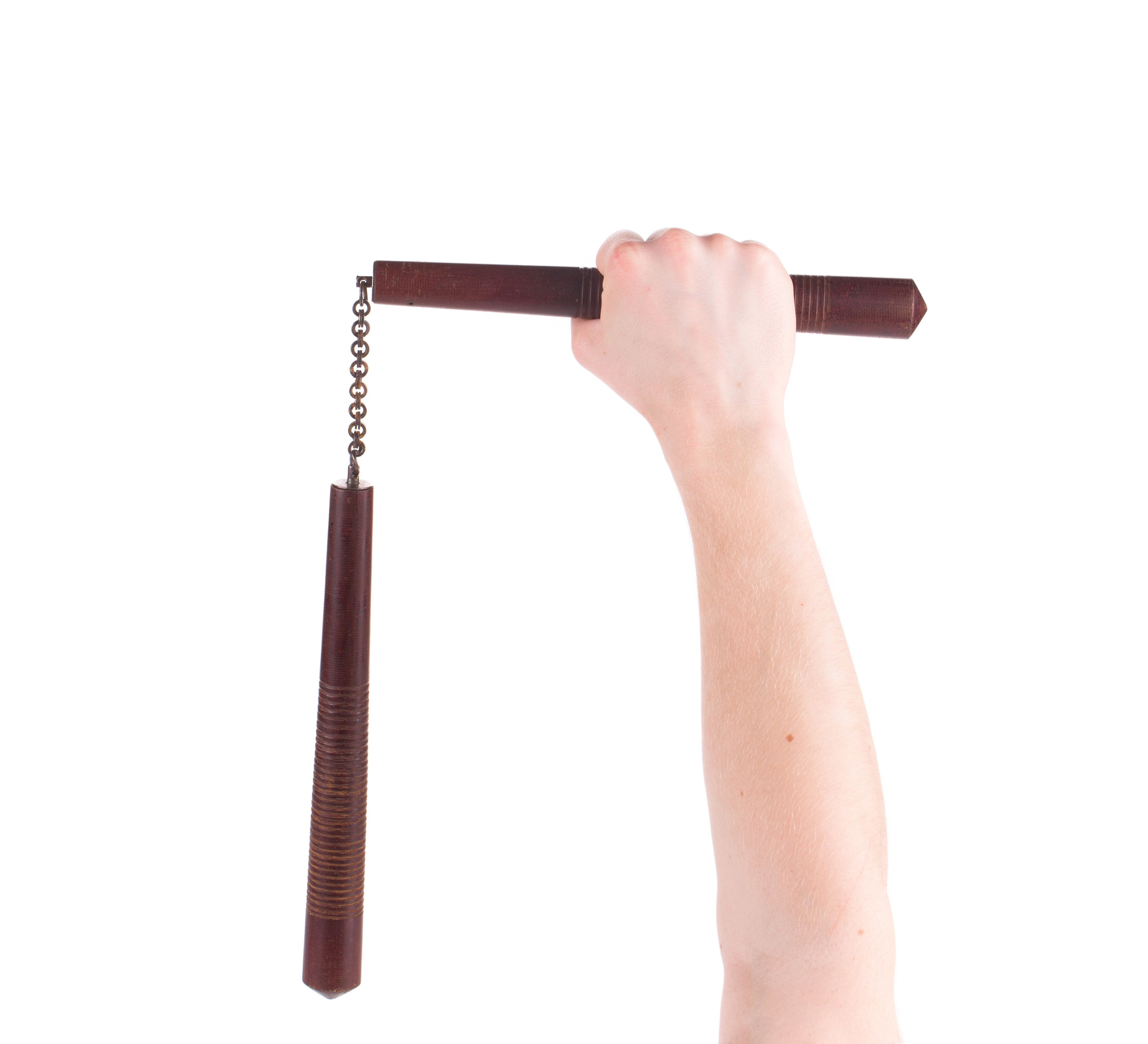 Hands hold martial arts nunchaku. Isolated on a white background.