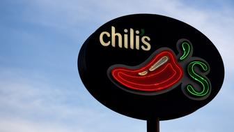 Signage stands on display outside a Brinker International Inc. Chili's Grill & Bar restaurant in San Antonio, Texas, U.S., on Monday, May 7, 2018. With commodity prices beginning to creep up for certain foods, grocery stores may have to raise prices. That would make it seem relatively cheaper to dine out at places like Chilis or Maggiano's, said Brinker International Inc. CEO Wyman Roberts. Photographer: Callaghan O'Hare/Bloomberg via Getty Images
