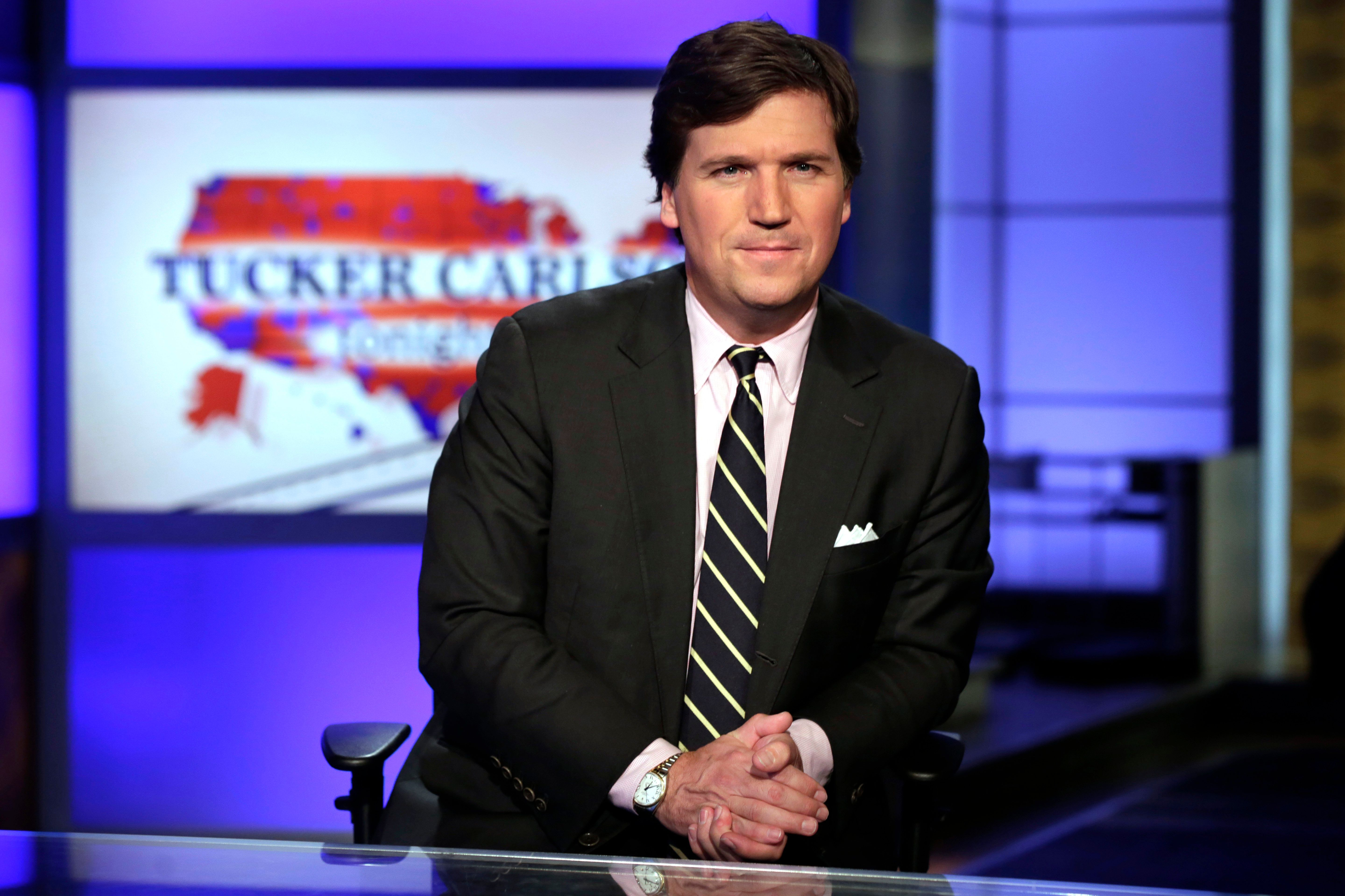 """FILE - In this March 2, 2017, file photo, Tucker Carlson, host of """"Tucker Carlson Tonight,"""" poses for photos in a Fox News Channel studio in New York. Carlson says he's shocked his segments this week on a South African policy on land reform should be considered an appeal to white nationalists - let alone spark an international incident. (AP Photo/Richard Drew, File)"""