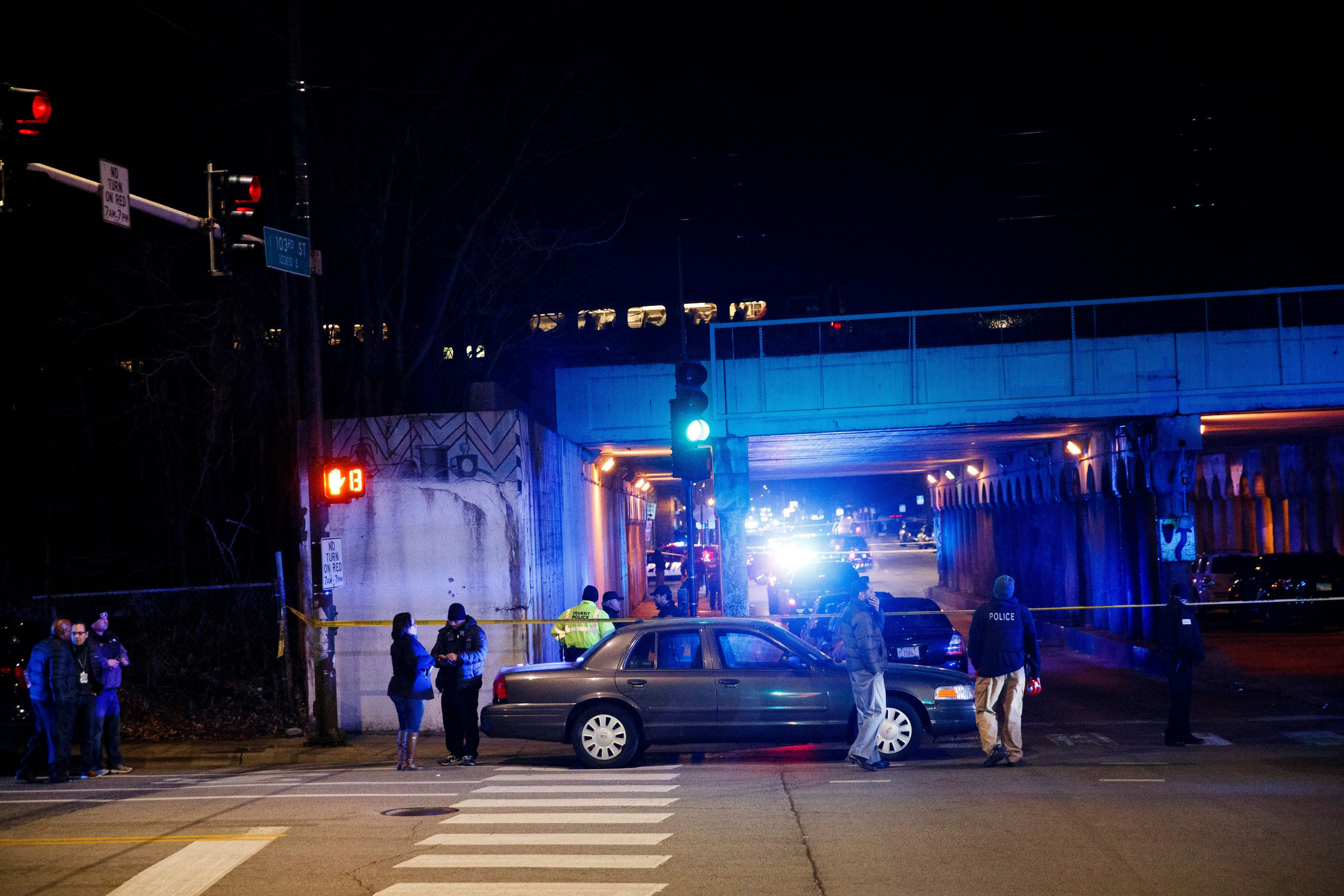 """Police investigate the scene where two officers were killed after they were struck by a South Shore train near 103rd Street and Dauphin Avenue on Monday, Dec. 17, 2018, in Chicago. Police spokesman Anthony Guglielmi posted on Twitter that the """"devastating tragedy"""" occurred when the officers were investigating a shots-fired call. (Armando L. Sanchez/Chicago Tribune via AP)"""