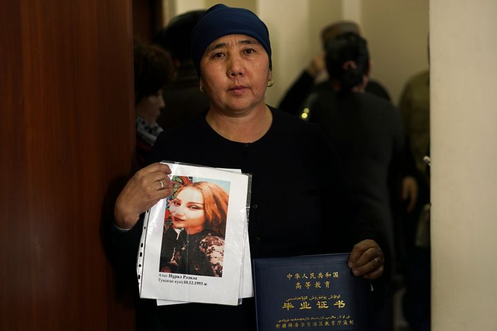 In this Dec. 6, 2018, photo, Nurbakyt Kaliaskar, the wife of a sheep herder, holds up a picture of her daughter, Rezila Nulal