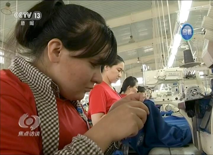 In this file image from undated video footage run by China's CCTV, Muslim trainees work in a garment factory in the Hotan Voc
