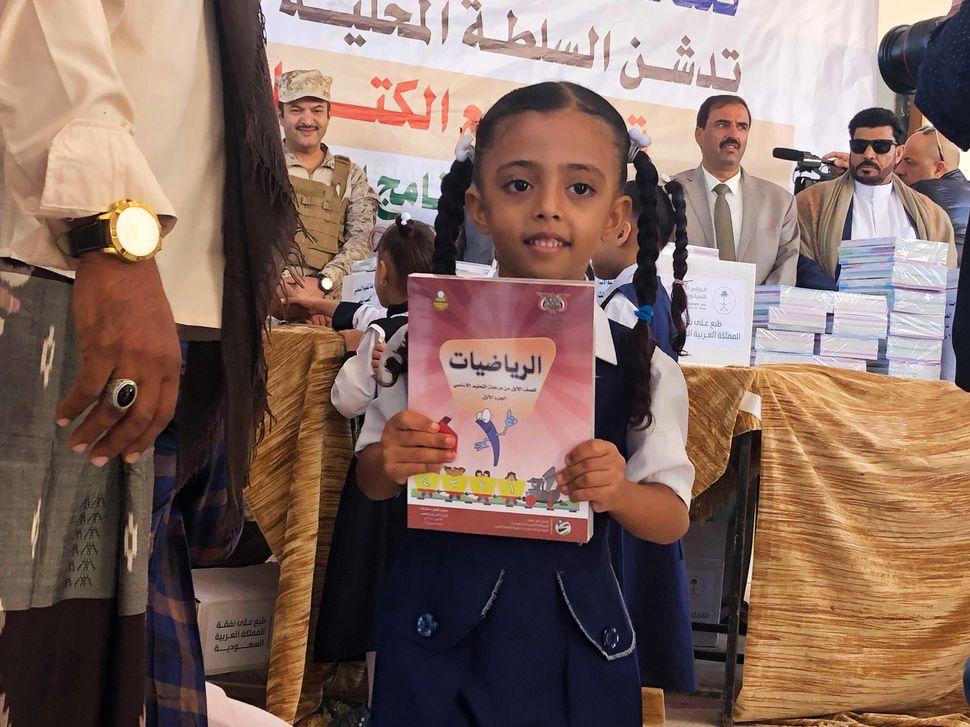 Ein Mädchen hält das neue Schulbuch in der Hand, das sie bekommen hat. Im Hintergrund links:Ali...