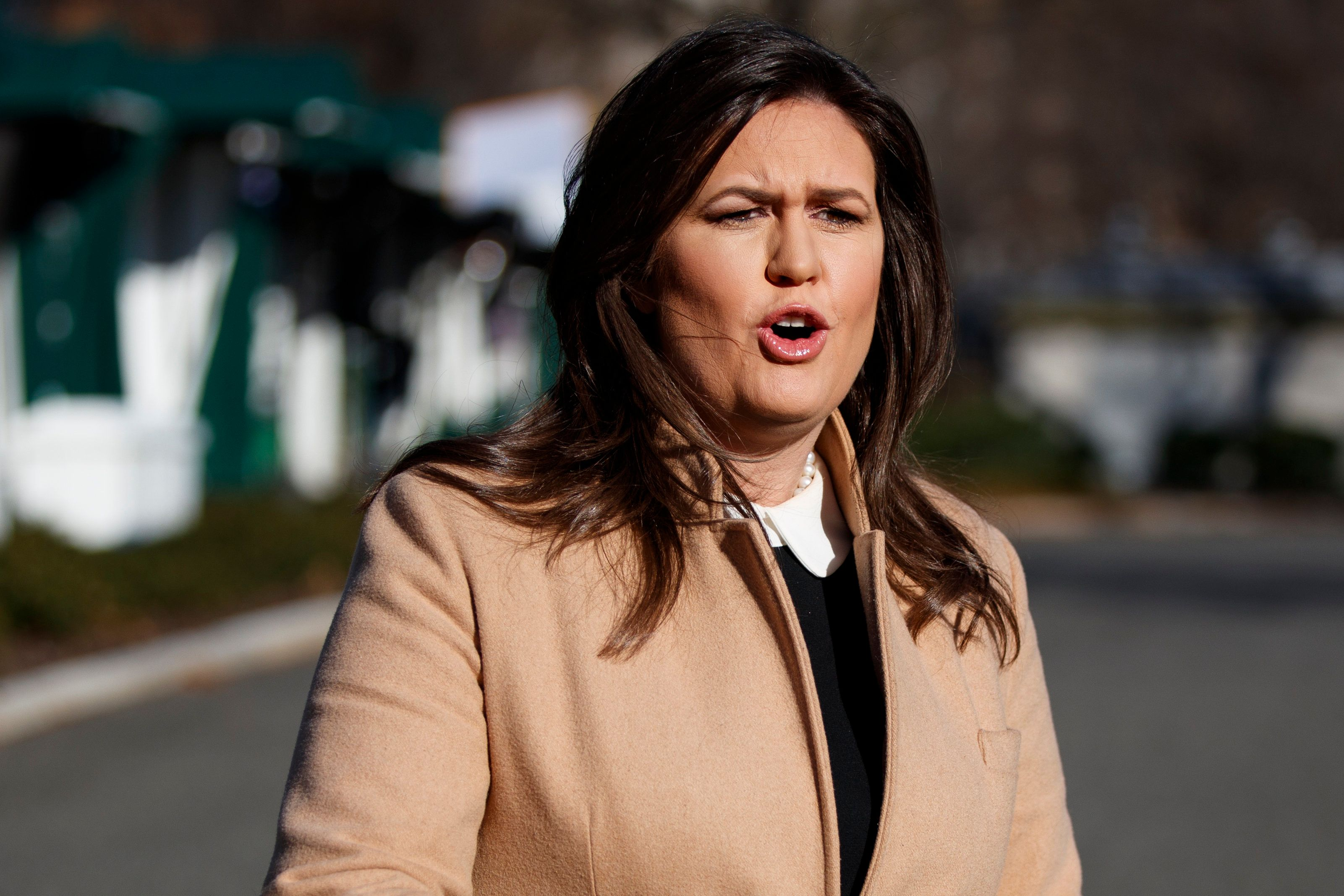 White House press secretary Sarah Huckabee Sanders talks with reporters outside the White House, Tuesday, Dec. 18, 2018, in Washington. (AP Photo/Evan Vucci)