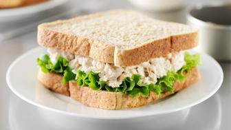 'Tuna salad sandwich made with mayonnaise, leaf lettuce and whole wheat bread. Jar of mayonnaise, tuna can and bread in out of focus background. More tuna sandwich...'