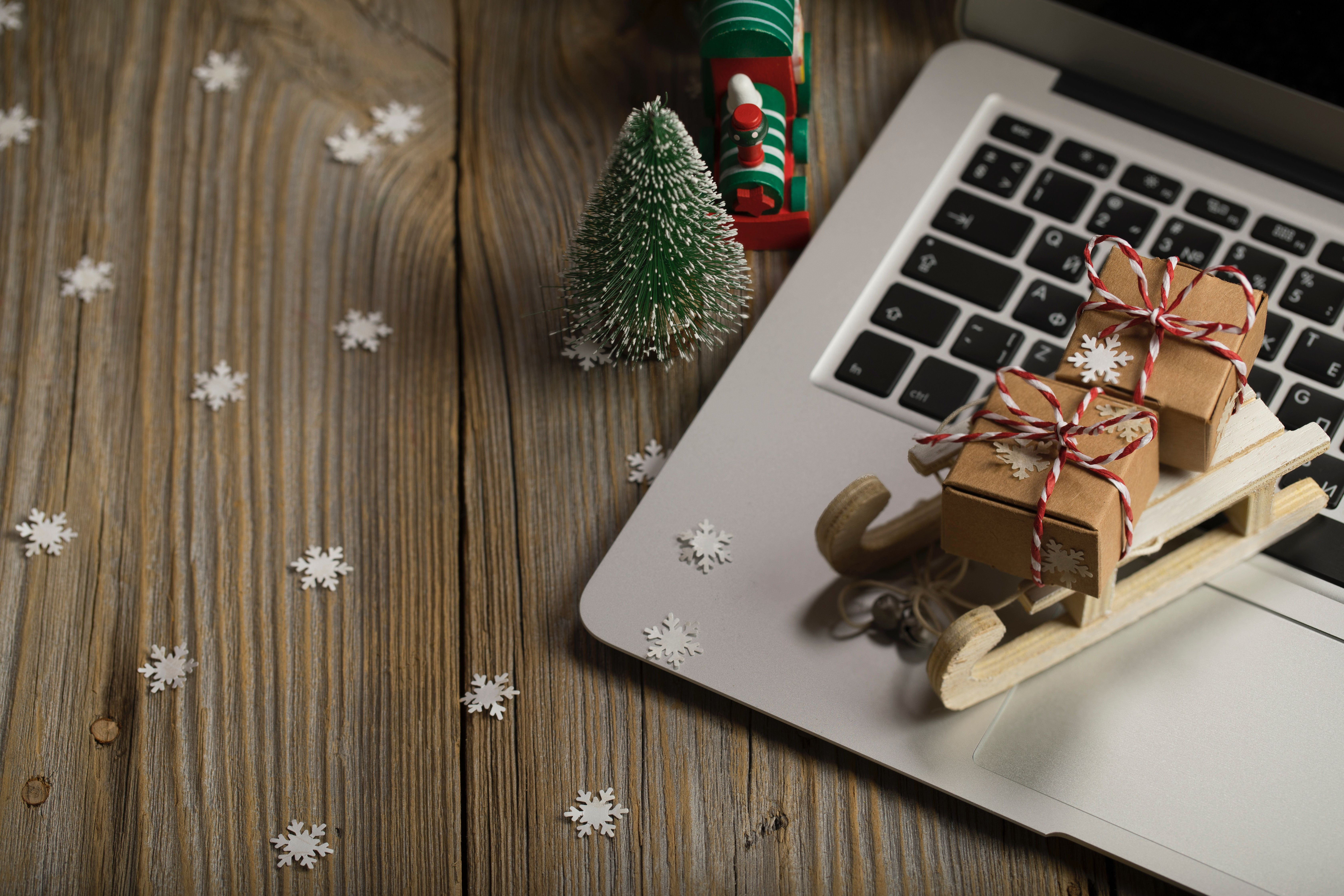 Small wooden sleigh with Christmas presents on a laptop. Closeup