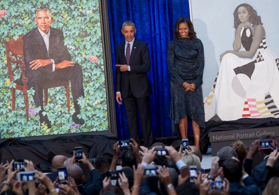 Former U.S. President Barack Obama and former first lady Michelle Obama stand beside their portraits after their unveiling at
