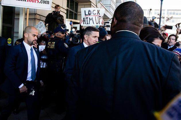 선고공판을 마치고 나오는 마이클 플린. 그의 뒷편으로 한 시위자가 '그를 가둬라'라고 적힌 피켓을 들고 있다. 플린은 2016년 대선 선거운동 당시 한 연설에서 민주당 힐러리 클린턴...