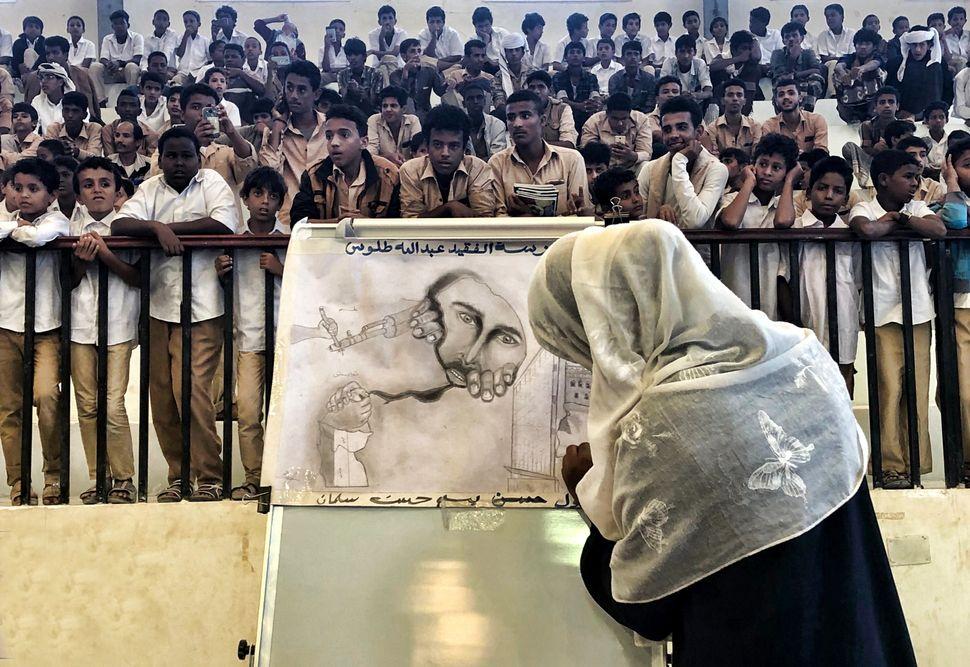 Bei einer großen Schulzeremonie zeichnet ein Mädchen, beobachtet von männlichen