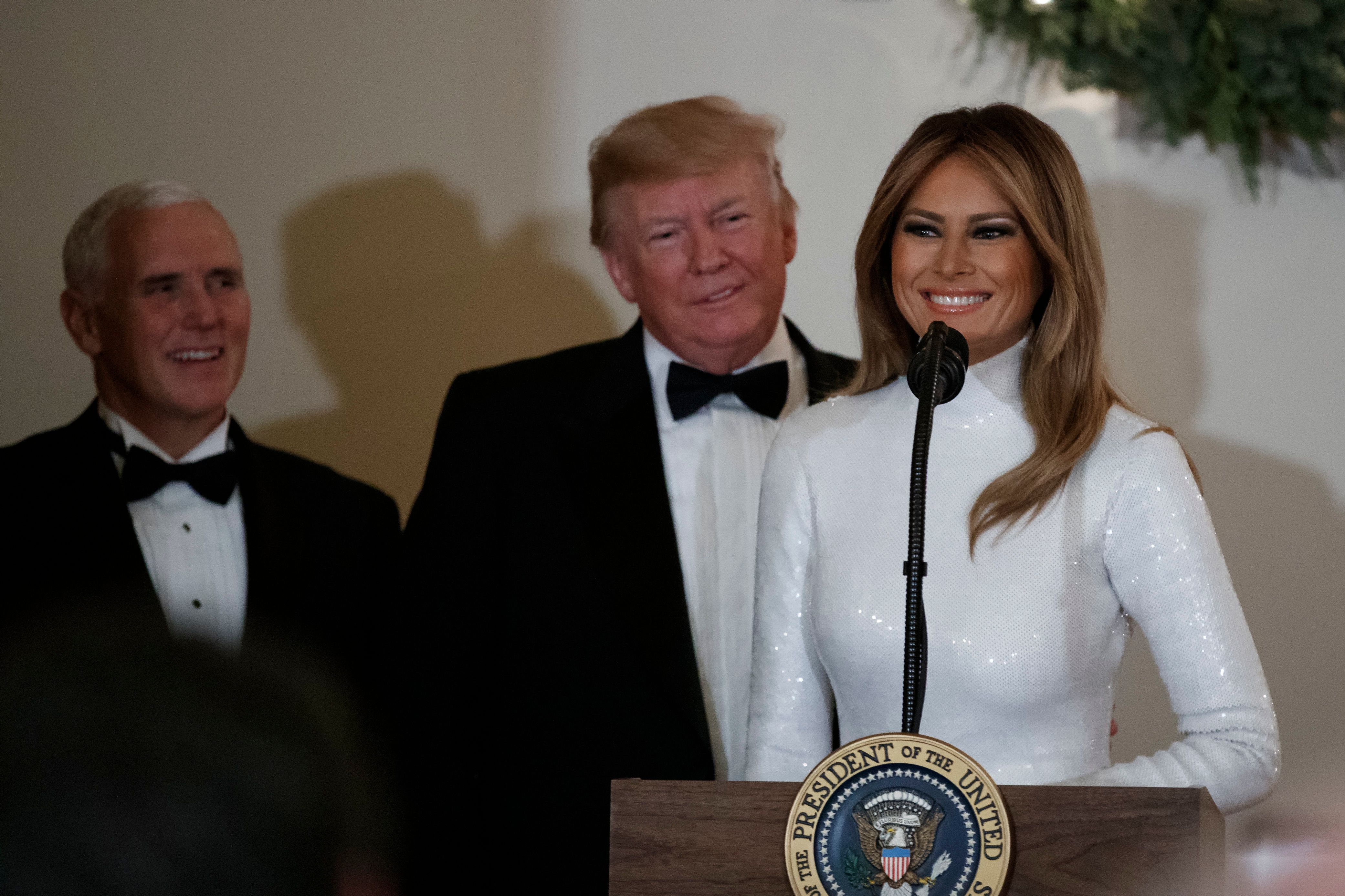 First lady Melania Trump, opined by President Donald Trump, and Vice President Mike Pence pauses as she speaks during the Congressional Ball in the Grand Foyer of the White House in Washington, Saturday, Dec. 15, 2018. (AP Photo/Carolyn Kaster)