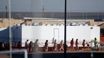 Migrant teens walk in a line through the Tornillo detention camp in Tornillo, Texas, Thursday, Dec. 13, 2018. The Trump administration announced in June 2018 that it would open the temporary shelter for up to 360 migrant children in this isolated corner of the Texas desert. Six months later, the facility has expanded into a detention camp holding thousands of teenagers. (AP Photo/Andres Leighton)