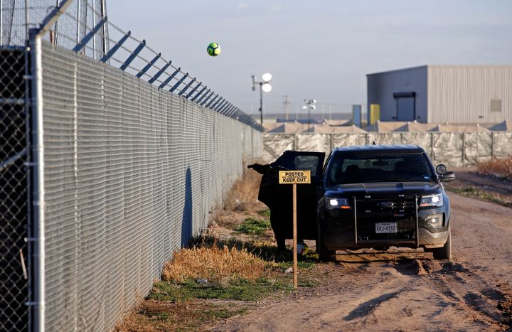 A private security guard throws a soccer ball back inside the Tornillo detention camp for migrant teens in Tornillo, Texas.&n