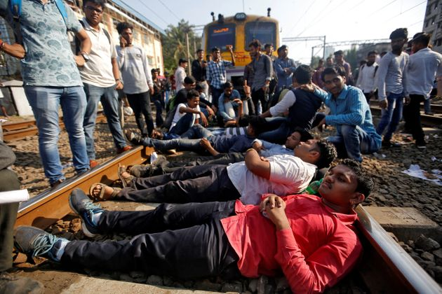Job seekers lie on railway tracks as they block train services during a protest demanding recruitment...