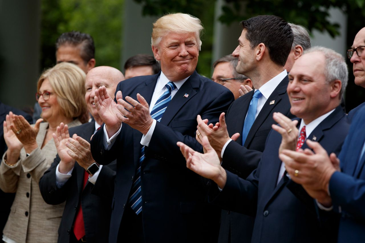 President Donald Trump and House Speaker Paul Ryan smile at each other at a celebration in the White House Rose Garden after the House pushed through a health care bill on May 4, 2017.