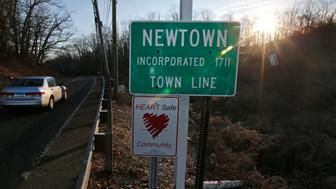 FILE - In this Saturday, Dec. 15, 2012 file photo, a car drives past the town line as the sun breaks the horizon, a day after the shooting of children and adults at Sandy Hook Elementary school in Newtown, Conn. When the name of the place you hold dear suddenly becomes synonymous with tragedy, the emotional impact can be searing and the aftereffects can linger for months, years, even generations. (AP Photo/Charles Krupa)