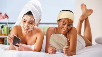 Two Hispanic young woman sharing beauty treatments at home or spa. Forest and sea at the background.