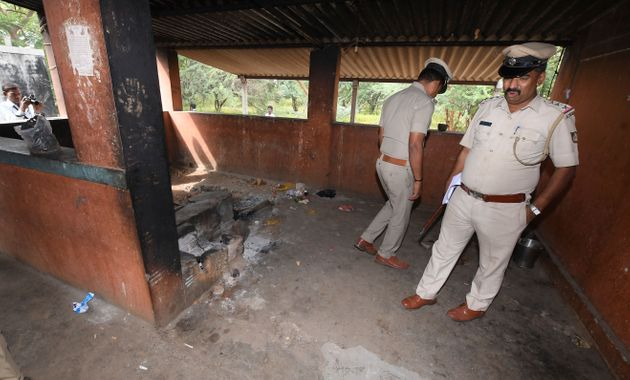 Policeman inspect the kitchen of a temple after a case of suspected food poisoning in Sulawadi village...