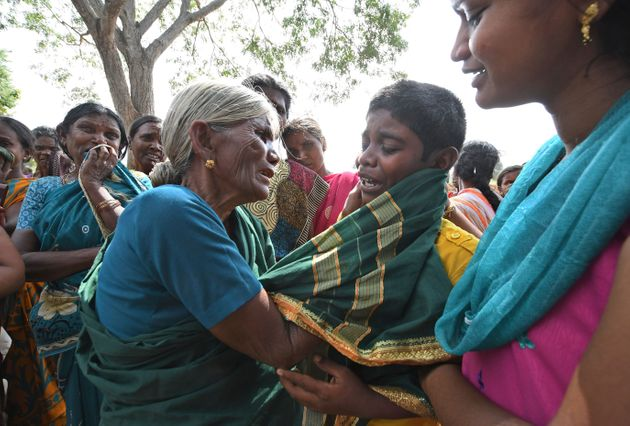 A boy cries consoled by his grandmother after his mother died of suspected food poisoning at Bidarahalli,...