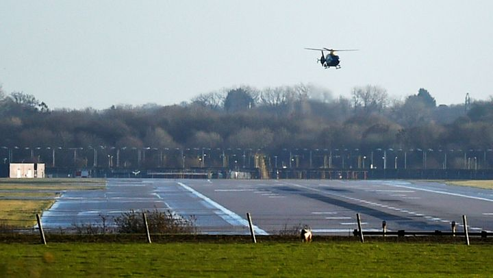 A helicopter conducts searches above Gatwick's runway on Thursday morning.