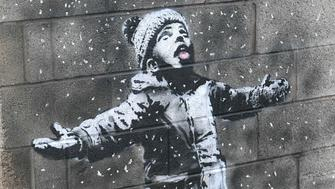 Artwork by street artist Banksy, Thursday Dec. 20, 2018, which appeared on a garage wall in Taibach, Port Talbot, south Wales. Street artist and social commentator Banksy has apparently popped up in Wales, leaving a new artwork on a garage in Port Talbot that references the town's air pollution. (Ben Birchall/PA via AP)