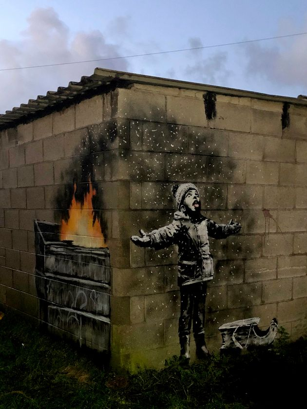 The full mural by Banksy reveals that the child is standing in ash from a dumpster