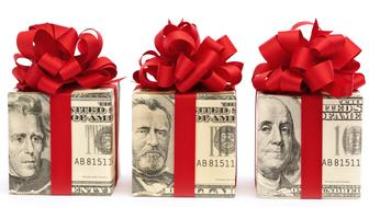 'Subject: Horizontal view of three square gift boxes, wrapped in twenty dollar, fifty dollar, and one hundred dollar United States currency bills and tied with red ribbons and bows. The bow color suggests a Christmas gift, bonus, birthday present, or special occasion. Isolated on a white background.'