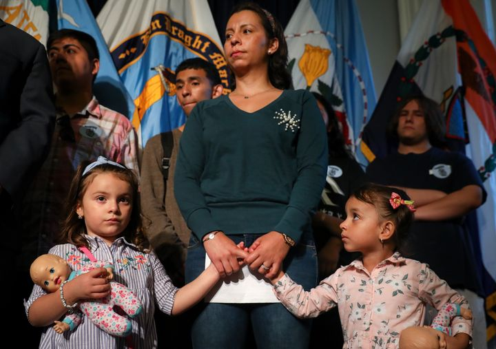 Sandra Chica holds the hands of her daughters during a rally and press conference in support of husband Pablo Villavicencio,