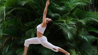 A woman doing a yoga pose on a garden (Ashwa Sanchalanasana)