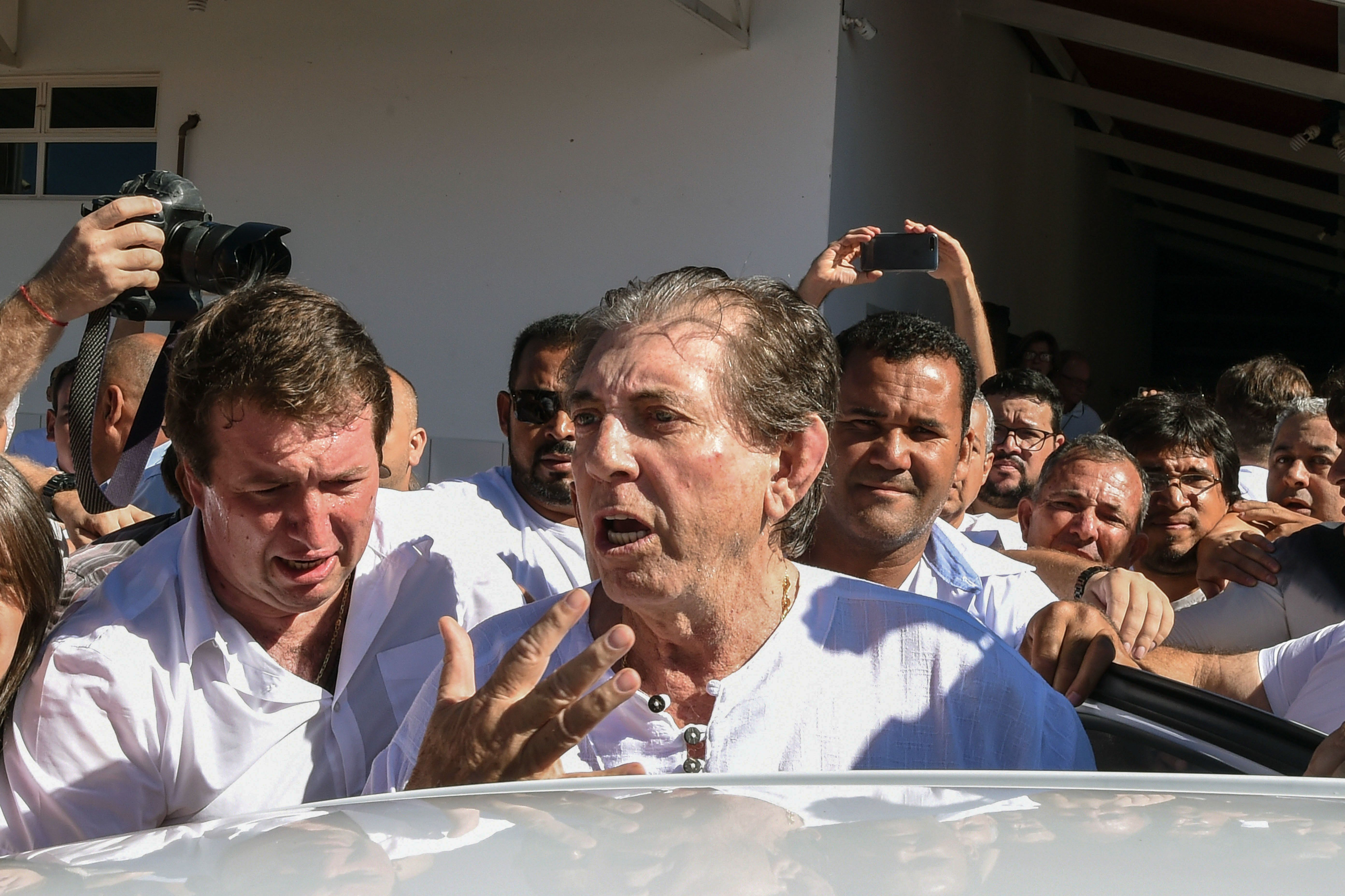 """João Teixeira de Faria (center), known as """"João de Deus,"""" or John of God, is escorted by supporters as he arriv"""