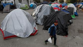 FILE - In this Dec. 14, 2018 file photo, a migrant walks into a migrant tent camp outside the closed Benito Juarez sports complex in Tijuana, Mexico. Central American migrants heading to the U.S. to apply for asylum will have to stay in Mexico while their claims are processed in the United States. Mexico agreed to the historic change on Thursday.   (AP Photo/Moises Castillo)