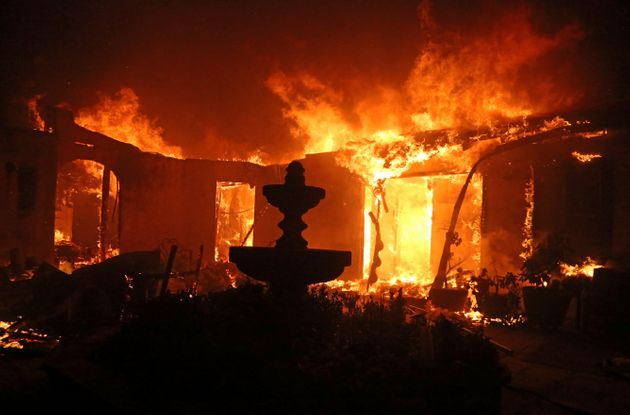 A Spanish-style home is consumed by wildfire flames on Dume Drive in Malibu, California, in
