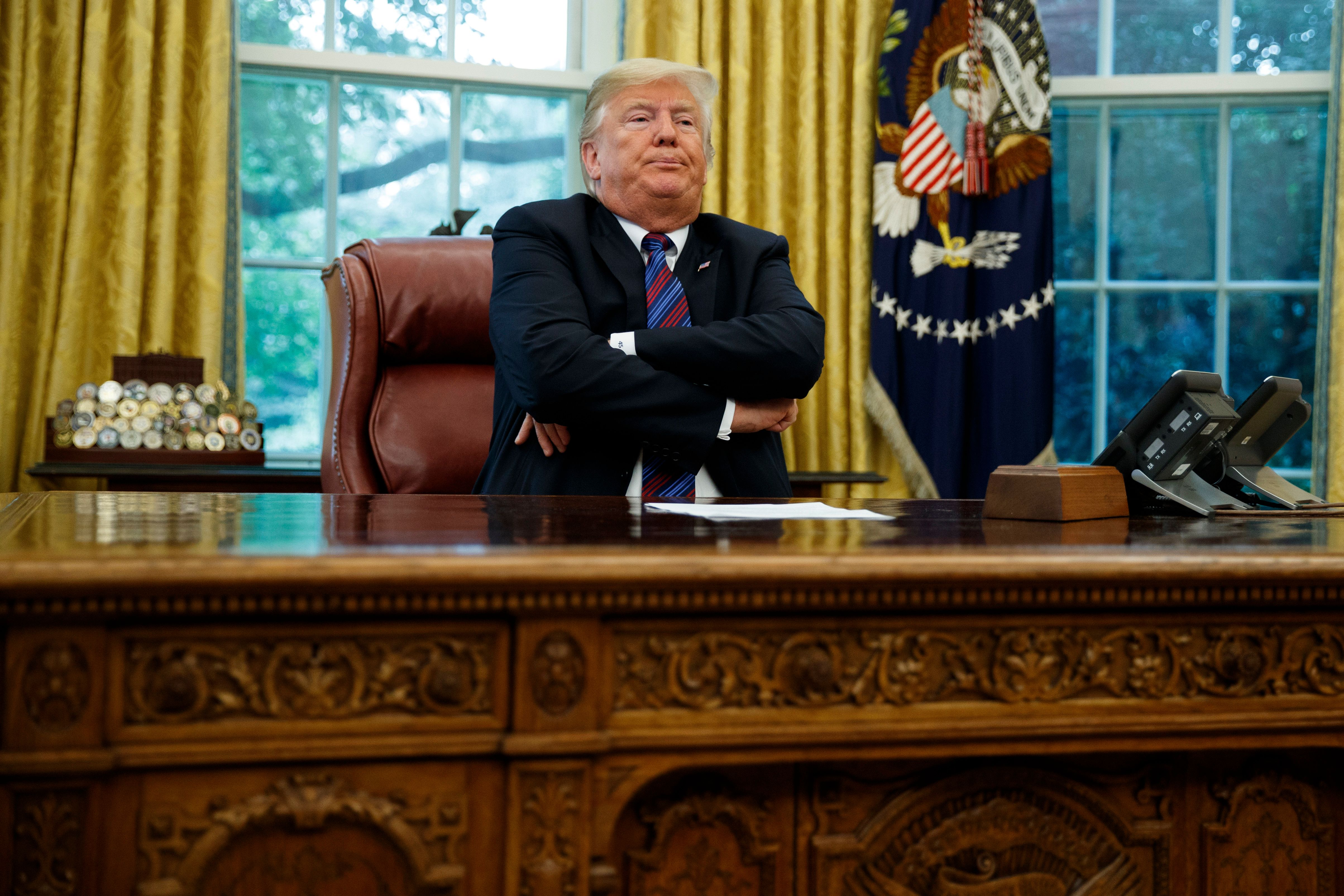 """President Donald Trump crosses his arms after speaking with Mexican President Enrique Pena Nieto on the phone about a trade agreement between the United States and Mexico, in the Oval Office of the White House, Monday, Aug. 27, 2018, in Washington. Trump has bowed to widespread pressure from veterans groups and others to do more to honor John McCain's death. Trump on Monday ordered flags at the White House and elsewhere lowered to half-staff until the six-term senator is buried Sunday. He also proclaimed """"respect"""" for McCain, with whom he feuded bitterly for years. It was a marked reversal from Trump's refusal to comment on McCain. Earlier Monday, the White House flag had been raised. (AP Photo/Evan Vucci)"""