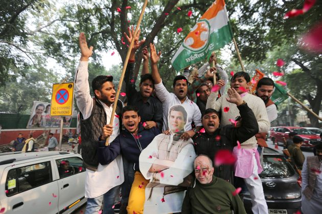 Congress party supporters hold a cut-out of party President Rahul Gandhi and celebrate outside the party...