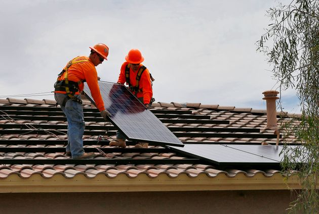 electricians Adam Hall, right, and Steven Gabert, install solar panels on a roof for Arizona Public Service...