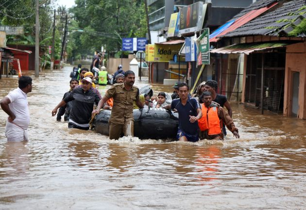 Rescuers evacuate people from a flooded area to a safer place in Aluva in Kerala, India on 18 August
