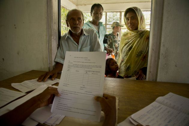 People whose names were left out in the NRC draft stand to collect forms to file appeals in Mayong, near...