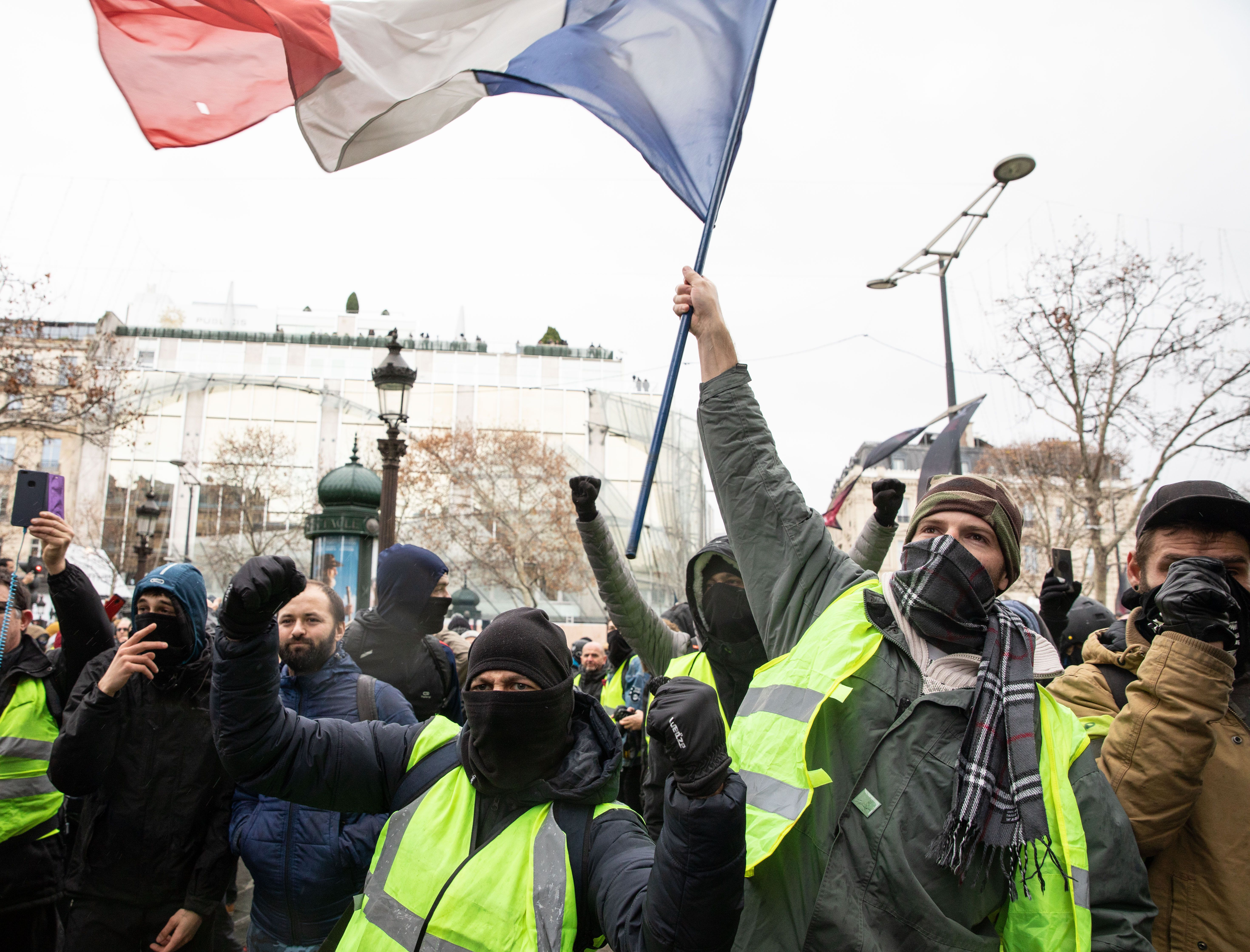 Protesters wearing yellow vests chant slogans and wave the French national flag, during the anti-government demonstrations in Paris, France, December 08, 2018. The withdrawal of French President Emmanuel Macron from implementing the Polluting Fuels tax, had very little to no effect on calming the tense situation in France as mass violent demonstrations continue to take place through several flashpoints across the country. In the French capital, members of the 'Yellow Jackets' movement along side high school students (protesting the education reform) and other citizens took to the streets.