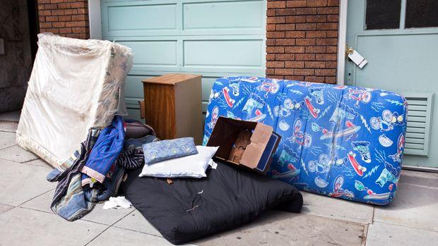 Personal household belongings abandoned on urban sidewalk. Horizontal.