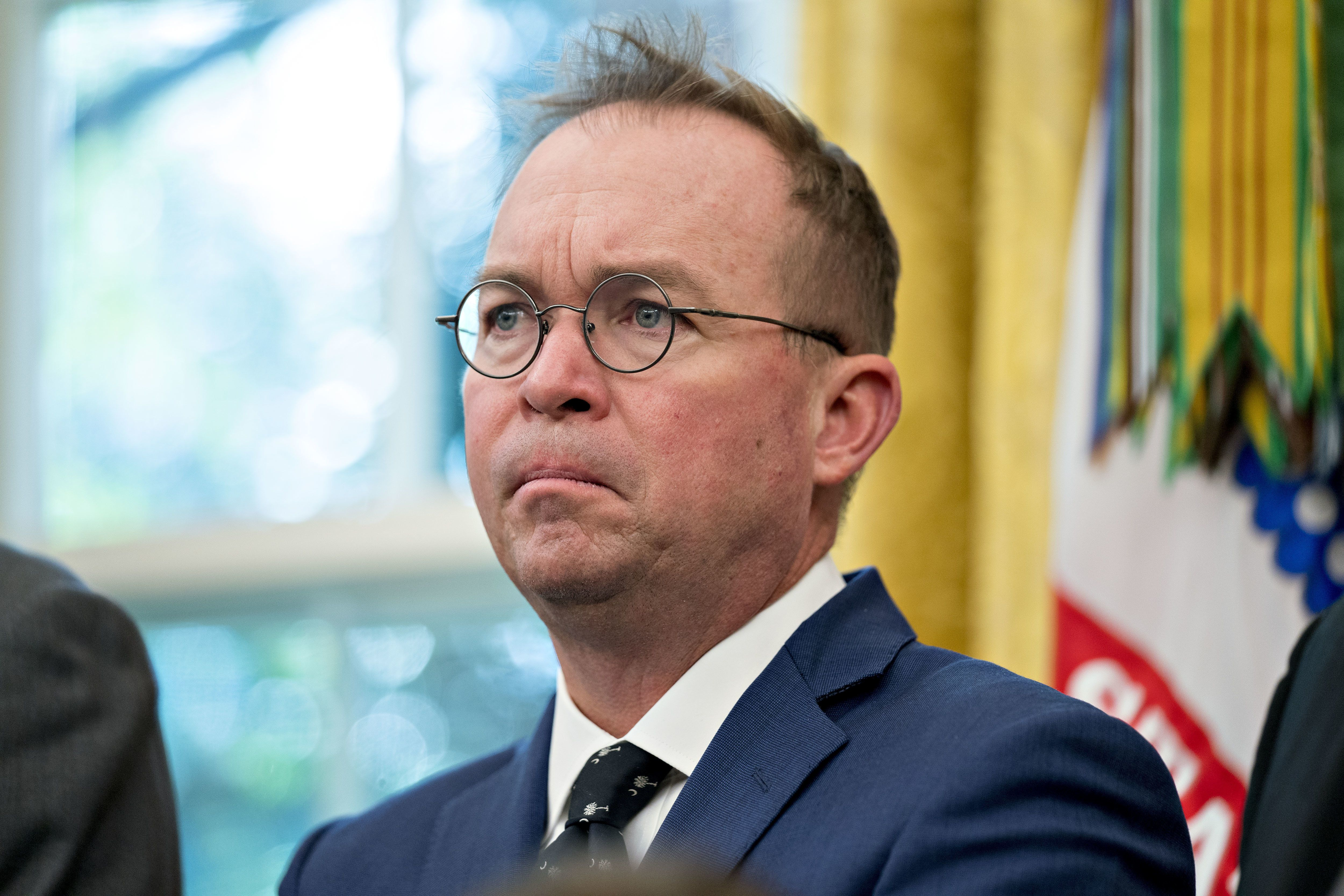 Mick Mulvaney, director of the Office of Management and Budget (OMB), listens during a meeting with U.S. President Donald Trump, not pictured, and workers in the Oval Office of the White House during a 'Cutting the Red Tape, Unleashing Economic Freedom' event in Washington, D.C, U.S., on Wednesday, Oct. 17, 2018. Trump plans to withdraw the U.S. from a treaty that gives Chinese companies discounted shipping rates for small packages sent to American consumers, another escalation of his economic confrontation of Beijing. Photographer: Andrew Harrer/Bloomberg via Getty Images